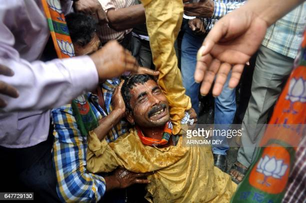 TOPSHOT Activists from India's Bharatiya Janata Party comfort a colleague on a street in Agartala on March 4 after he was injured during a rally held...
