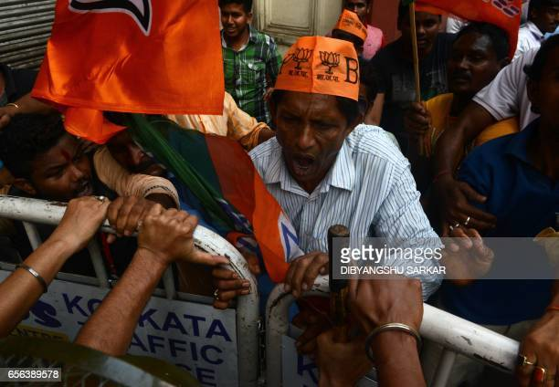 Activists from India's Bharatiya Janata Party shout slogans as they attempt to break through a police barricade during a rally in Kolkata on March 22...