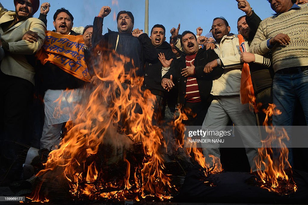Activists from India's main opposition Bharatiya Janata Party (BJP) burn an effigy of Indian Home Minister Sushilkumar Shinde's as they demand his resignation for alleging that the BJP and The Rashtriya Swayamsevak Sangh (RSS) were behind attacks on non-Hindus during a demonstration in Amritsar on January 24,2013. BJP leaders have demanded the resignation of Shinde for the comments and they want an apology from the congress led government. AFP PHOTO/NARINDER NANU