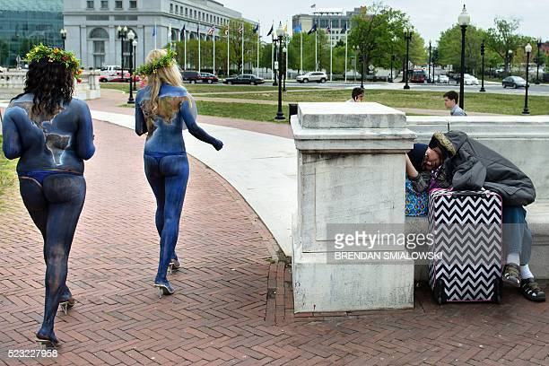 Activists from People for the Ethical Treatment of Animals walk past a homeless person while celebrating Earth Day and promoting a vegan diet in...