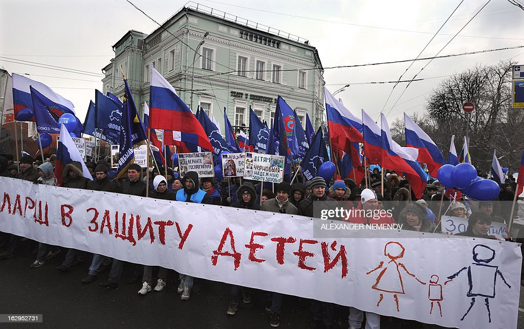 Activists from pro-Kremlin children's advocacy groups march through Moscow on March 2, 2013 to call on authorities to ban all foreign adoptions and demand the return of an adopted boy whose brother died in Texas. The banner reads 'The March for Protection of the Children'. AFP PHOTO / ALEXANDER NEMENOV