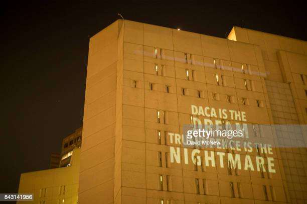 Activists from RefuseFascismorg project antiTrump administration messages onto the side of the Metropolitan Detention Center where many undocumented...
