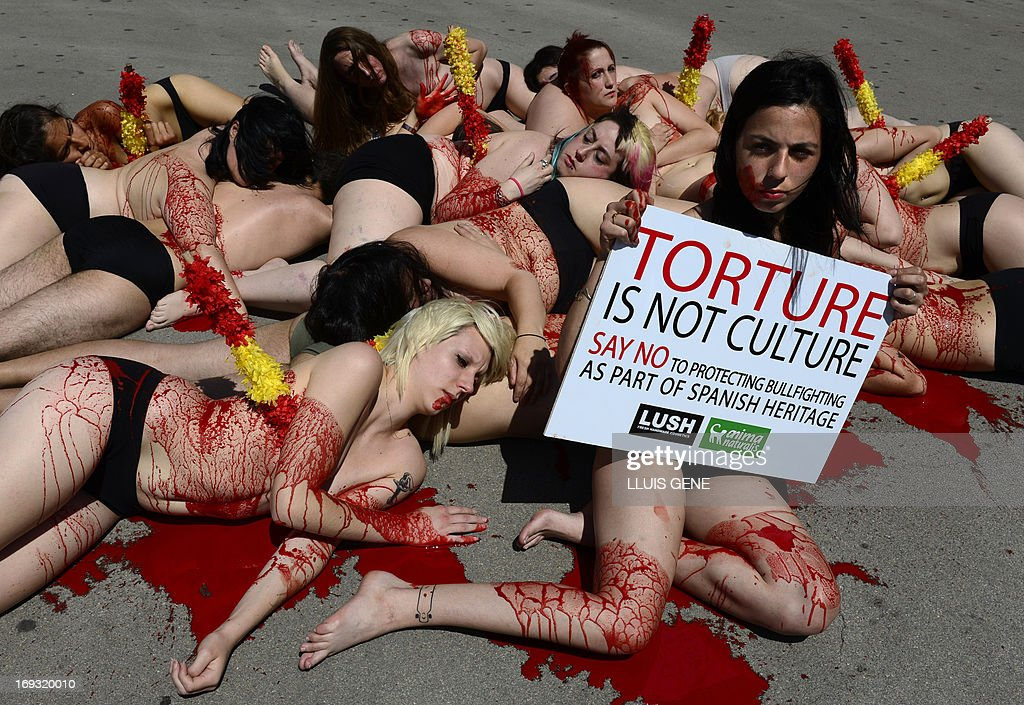 Activists from the animal-rights group 'AnimaNaturalis' protests half-naked covered with fake blood against bullfighting and asking the government not to protect bullfighting as part of Spain's heritage, on May 23, 2013 in Barcelona. AFP PHOTO/LLUIS GENE