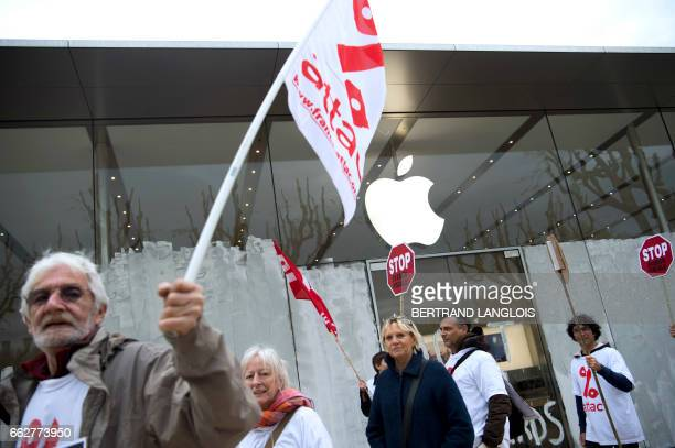 Activists from the Association for the Taxation of financial Transactions and Citizen's Action hold flags after painting in white the facade of an...