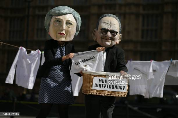 Activists from the communitybased organization Avaaz satirically posing as Britain's Prime Minister Theresa May and media mogul Rupert Murdoch...