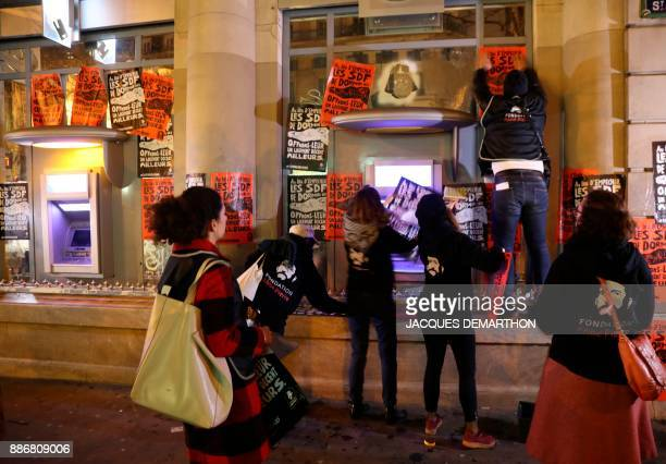 Activists from the Fondation Abbe Pierre foundation stick leaflets and posters on a bank in Paris on December 6 to highlight the use of 'antihomeless...