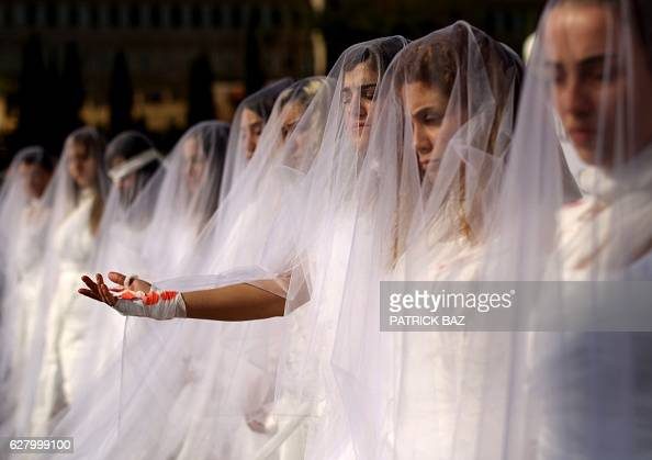 TOPSHOT Activists from the Lebanese NGO Abaad a resource centre for gender equality dressed as brides and wearing injury patches hold a protest in...