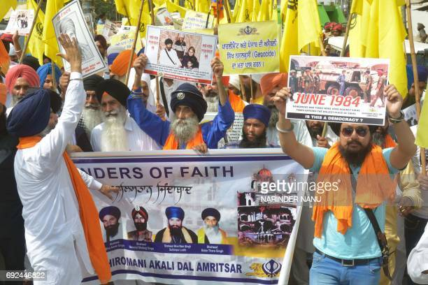 Activists from the Sikhcentric political party Shiromani Akali Dal hold placards and religious flags during a march on the eve of the 33th...