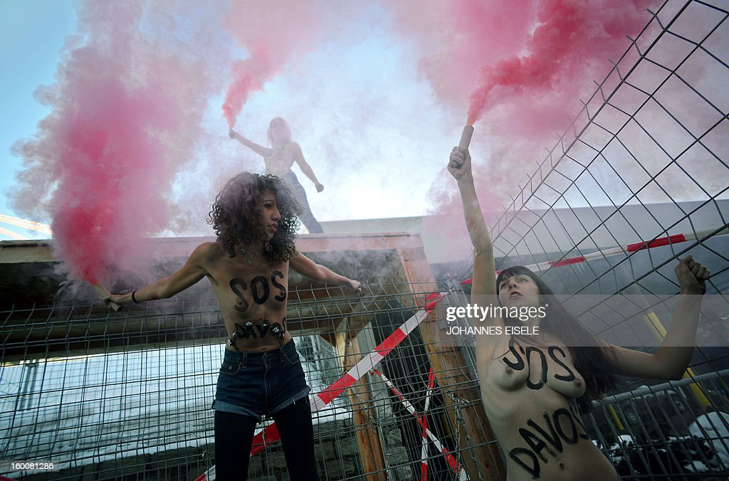 Activists from the Ukrainian feminist group FEMEN shout slogans during a topless protest on January 26, 2013, against the World Economic Forum (WEF) 2013 annual meeting in the Swiss resort of Davos.