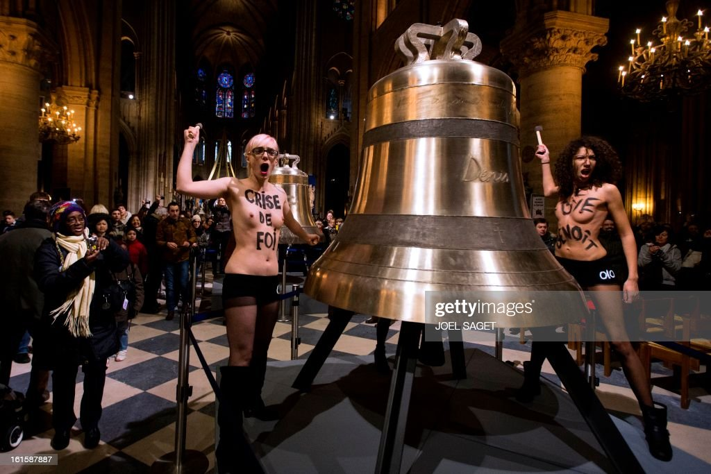 Activists from the women's rights organisation Femen protest in front of the new eight bronze bells displayed in the nave of Notre-Dame de Paris Cathedral in Paris February 12, 2013. According to activists, the protest was organized to celebrate the resignation of Pope Benedict and the French parliament s decision to approve a draft law allowing same-sex marriage. AFP PHOTO JOEL SAGET