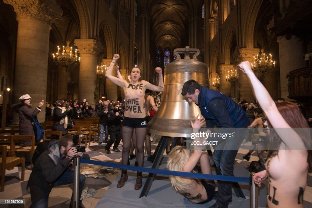 Activists from the women's rights organisation Femen protest in front of the new eight bronze bells displayed in the nave of Notre-Dame de Paris Cathedral in Paris February 12, 2013. According to activists, the protest was organized to celebrate the resignation of Pope Benedict and the French parliament s decision to approve a draft law allowing same-sex marriage.