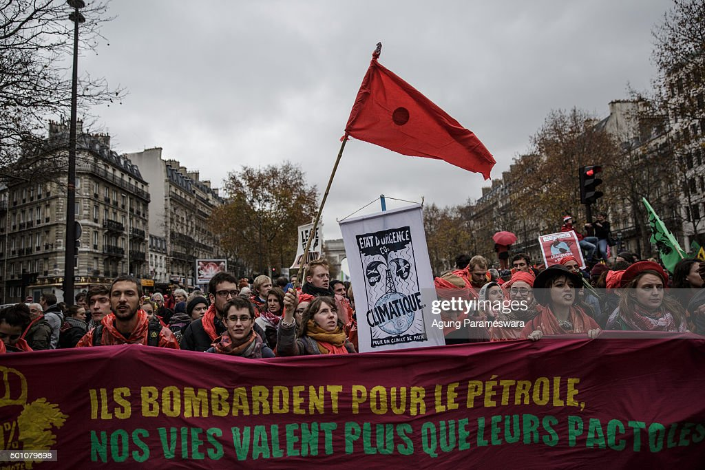 Activists gather as they shouts and hold banner during a demonstration near the Arc de Triomphe at the Avenue de la Grande Armee boulevard on December 12, 2015 in Paris, France. The final draft of a 195-nation landmark agreement on climate has been submitted at the United Nations conference on climate change COP21, aimed at limiting greenhouse gas emissions and keeping planetary warming below 2.0 degrees Celsius.