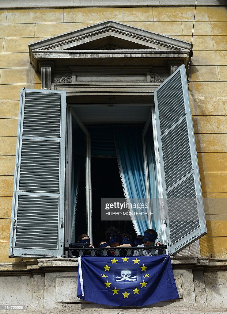 Activists hang a European Union flag with a jolly rodger painted on it after occupying the European System of Central Banks (ESCB) and eurosystem offices of the Bank of Italy to protest against the austerity measures across Europe and to ask for income to all on October 16, 2013 in Rome. AFP PHOTO /Filippo MONTEFORTE