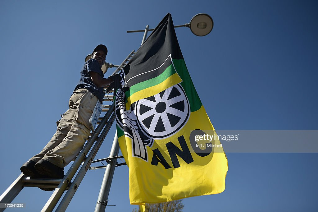 ANC activists hang flags on lamp post near the Vilakazi Street home of Nelson Mandela, 94, who is being treated for a recurring lung infection in hospital on July 3, 2013 in Johannesburg, South Africa. The anti-apartheid icon and Nobel Peace Prize laureate has been in a critical condition at the hospital for more than three weeks.