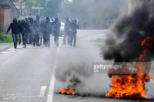 Activists head towards burnt tyres to face French gendarmes during an important evacuation operation started on October 16 of houses squatted by...