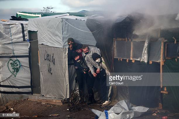 Activists hide from a water cannon as part of the 'jungle' migrant camp is cleared on February 29 2016 in Calais France The French authorities have...