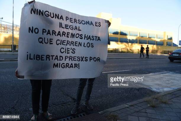 Activists hold a banner as they take part in a protest in front of Immigrant Detention Center of Aluche in Madrid