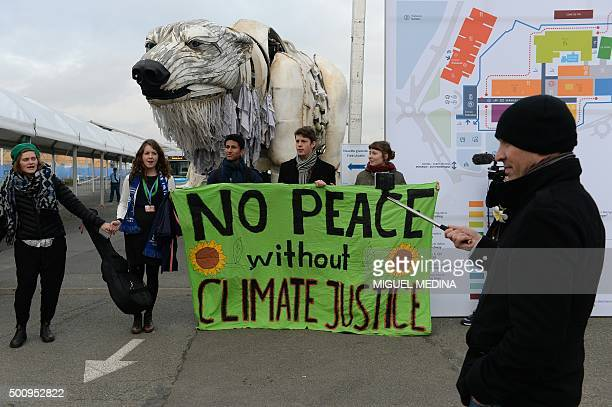 Activists hold a banner reading 'No peace without climate justice' in front of a giant polar beer puppet called Aurora by environmental organization...