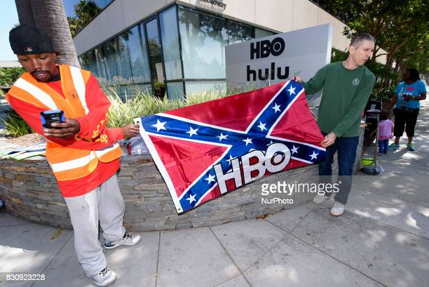 Activists hold a Confederate flag with the HBO logo in protest of HBOs new series in development Confederate Santa Monica California on August 12...