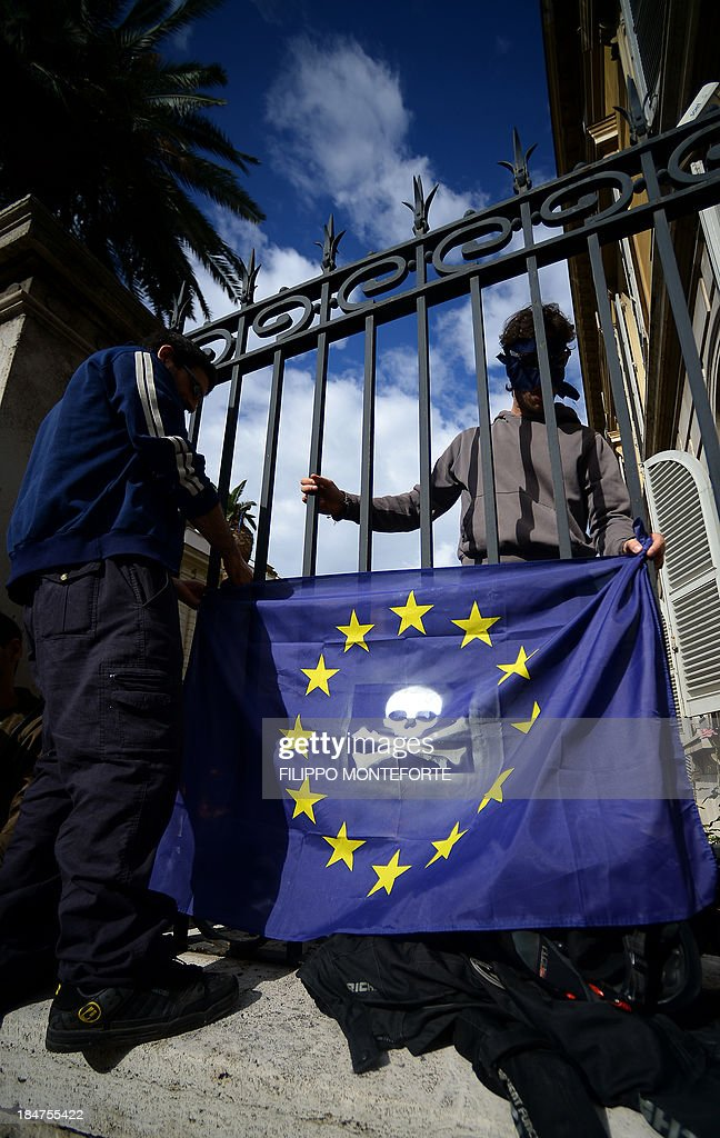 Activists hold a European Union flag with a jolly rodger painted on after occupying the European System of Central Banks (ESCB) and eurosystem offices of the Bank of Italy to protest against the austerity measures across Europe and to ask for income to all on October 16, 2013 in Rome. AFP PHOTO /Filippo MONTEFORTE