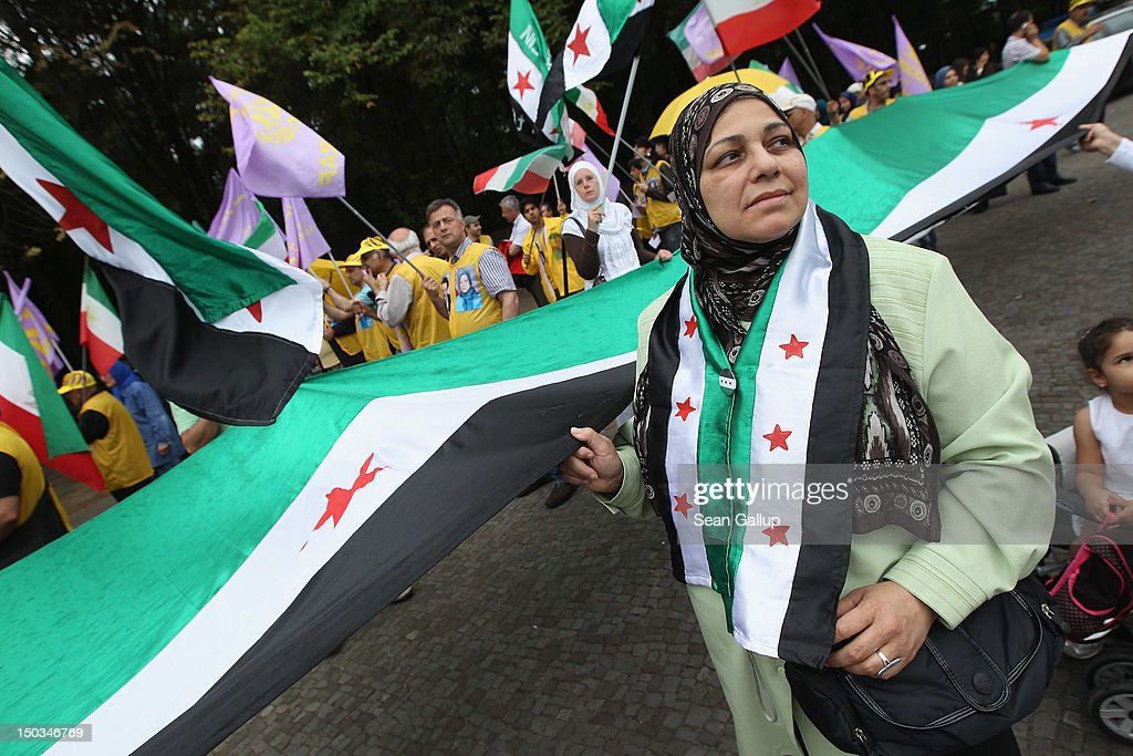 Activists hold a giant Syrian opposition flag at a demonstration of mostly expatriate Iranian opposition activists protesting against Iranian support of the government of Syrian President Bashar Assad on August 16, 2012 in Berlin, Germany. Meanwhile the Organization of Islamic Cooperation suspended Syria's membership during its current summit in Mecca.