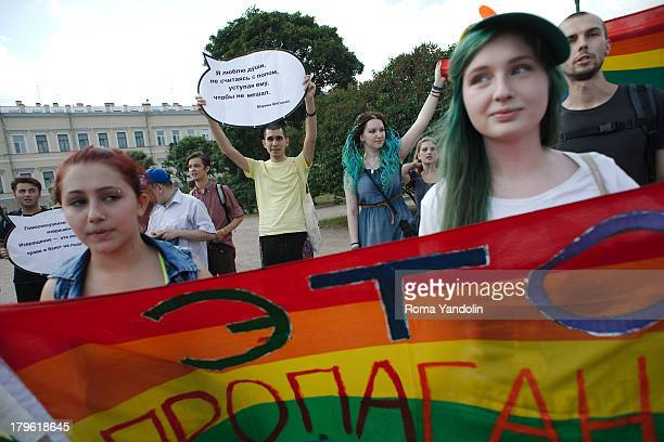 CONTENT] LGBT activists hold a rainbow flag during the Gay Pride rally in St Petersburg Russia Demonstrating LGBT activists and the Russian...