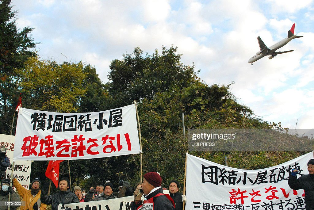 Activists hold a rally near Narita international airport in Narita, suburban Tokyo on November 28, 2012 to protest against the removal of their huts originally built in 1971 during radical protests against the building of the airport. Work crews began demolishing two huts built in 1971 on land earmarked for Narita Airport, structures that were a legacy of bloody protests that left police officers dead as homemade bombs were tossed by leftist students, activists and farmers who said they were the victims of a land grab in rapidly-modernising Japan. JAPAN OUT AFP PHOTO / JIJI PRESS
