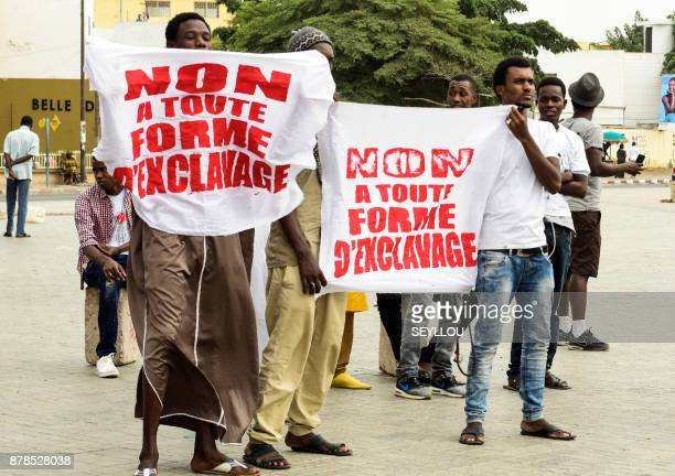 activists hold banners reading 'No to any form of slavery' during a gathering against slavery on November 24 2017 on Place de l'Obelisque in Dakar...