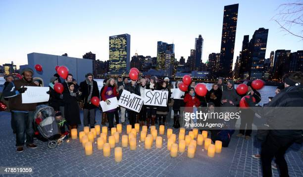 Activists hold red balloons and signs during the 'With Syria' campaign to mark the third anniversary of the start of the Syrian conflict at Roosevelt...