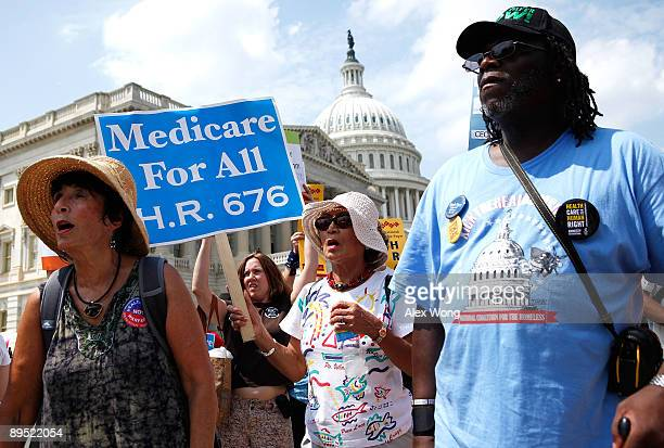 Activists hold signs as they march on Capitol Hill after a rally on healthcare July 30 2009 in Washington DC Activists gathered to rally lawmakers on...
