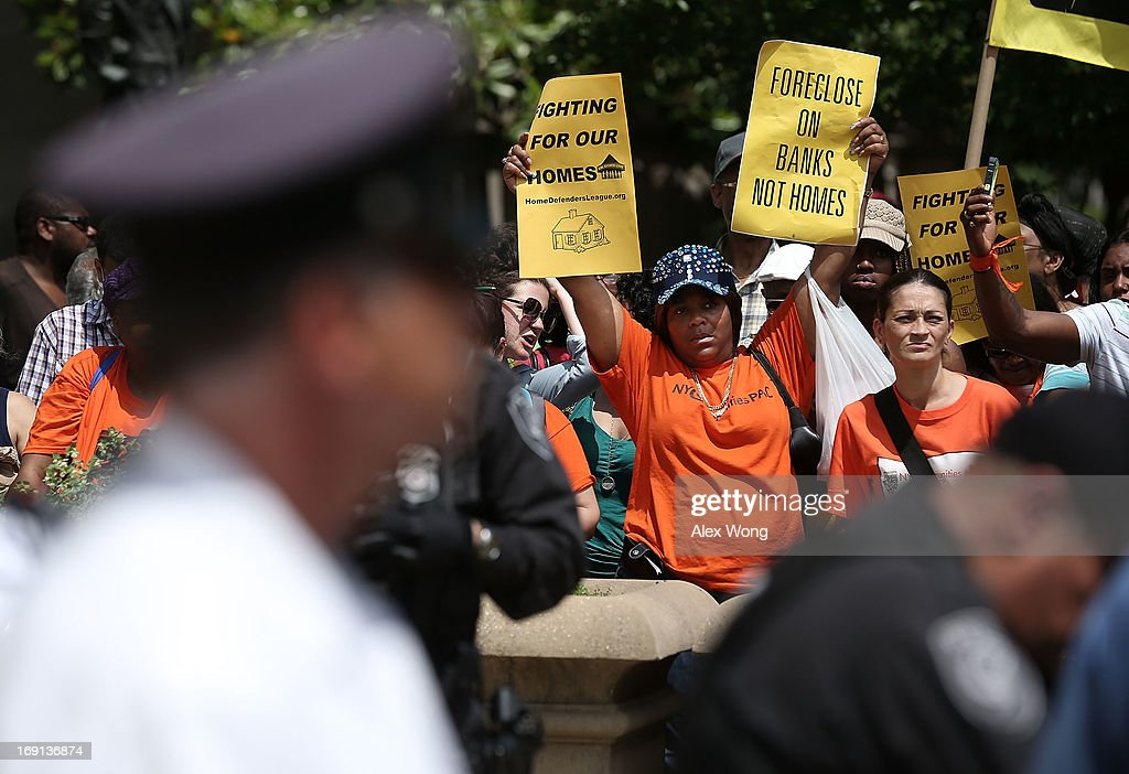 Activists hold signs during a protest outside the U.S. Justice Department May 20, 2013 in Washington, DC. Homeowners and activists from Home Defenders League and Occupy Homes joined the protest to demand that Attorney General Eric Holder 'hold Wall Street Banks that ravaged America's economy accountable.'