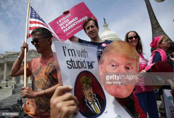 Activists hold signs during a Stop 'Trumpcare' rally May 4 2017 in front of the Capitol in Washington DC Congressional Democrats joined activists for...