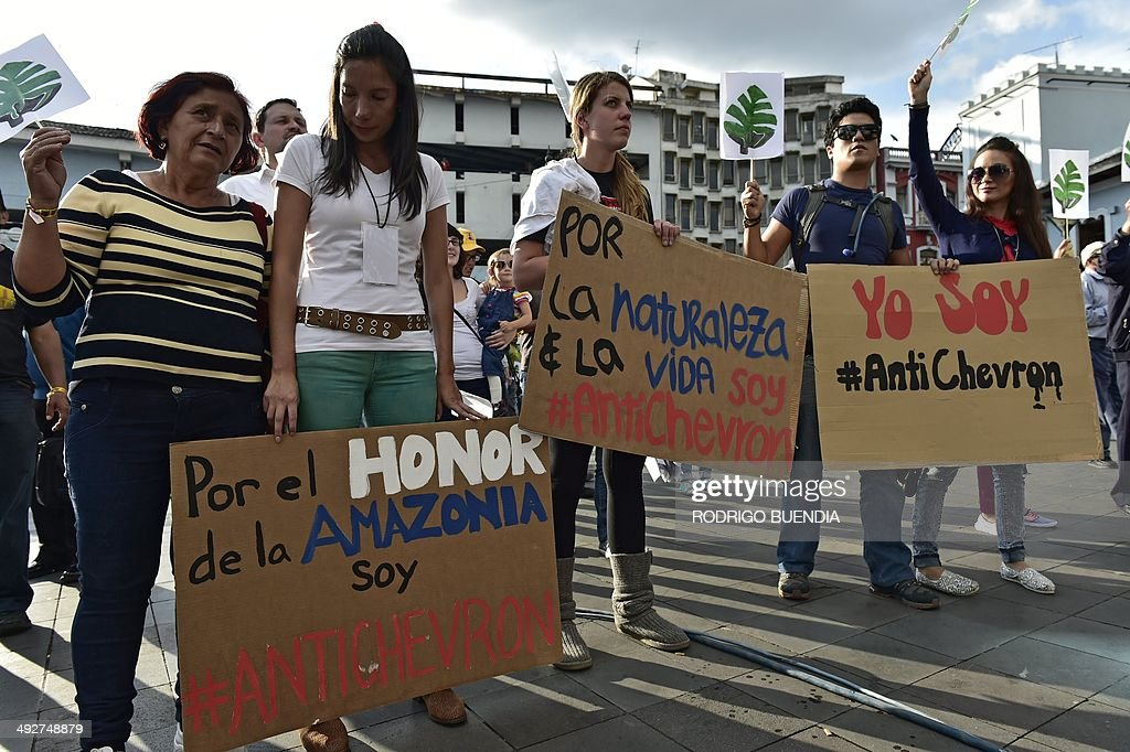 Activists hold signs reading 'For Amazonia's honor I am AntiChevron' 'For nature life I am Antichevron' and ' I am AntiChevron' during a protest...