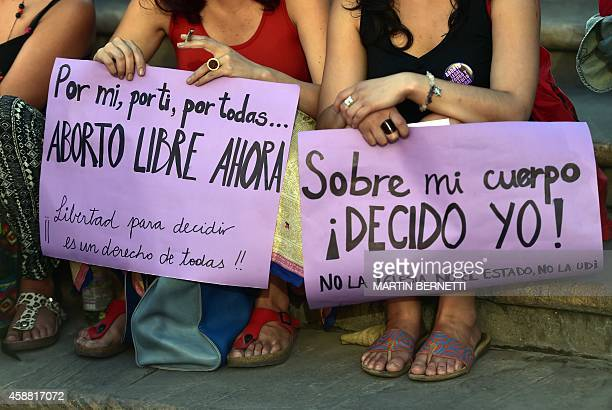 Activists hold signs reading 'For me for you for allFree abortion now' and 'On my body I decide' as they take part in a proabortion demo in front of...