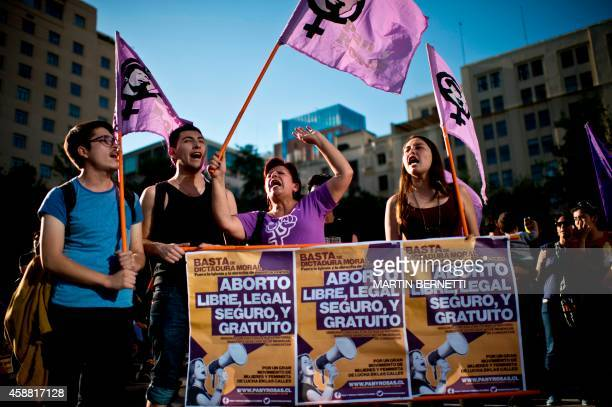 Activists hold signs reading 'Free safe and legal abortion' as they take part in a proabortion demo in front of La Moneda presidential Palace in...