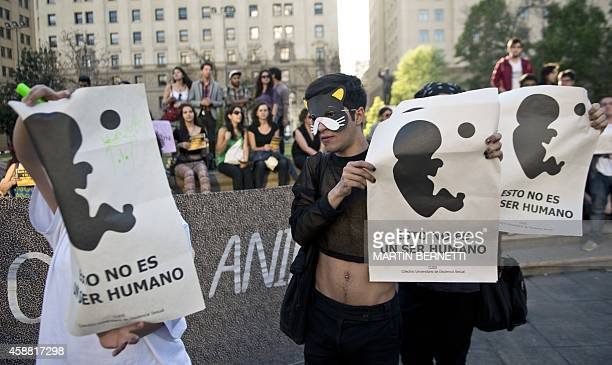 Activists hold signs reading 'This is not a human being' as they take part in a proabortion demo in front of La Moneda presidential Palace in...