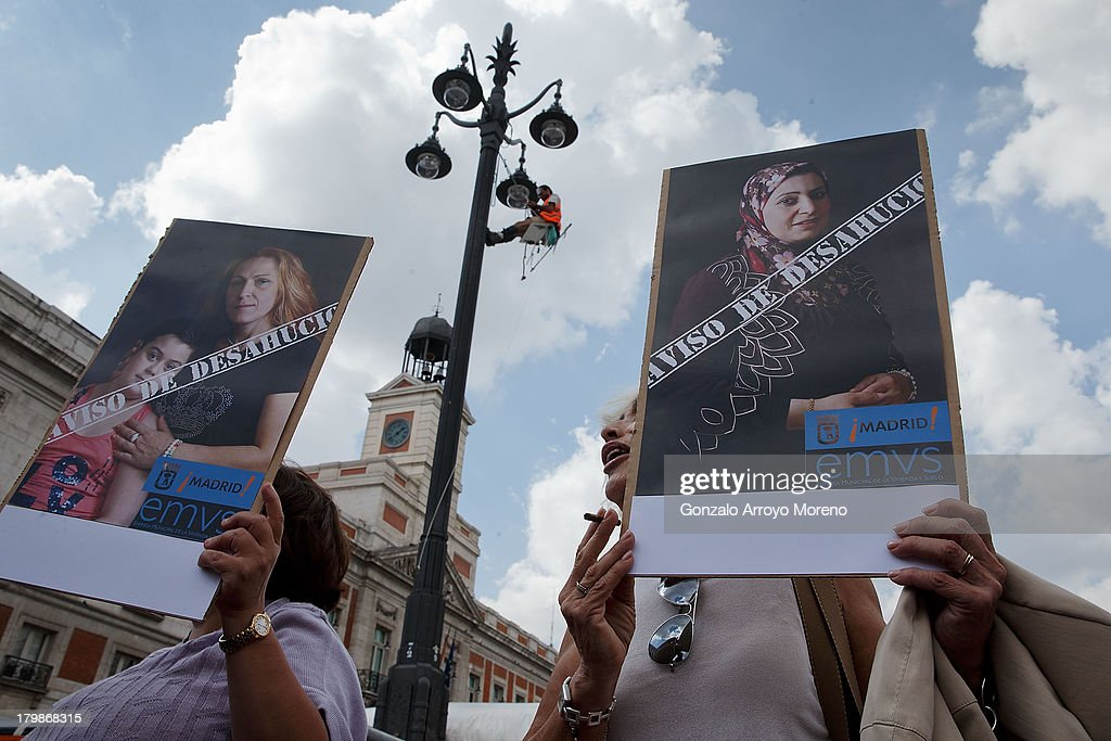 activists hold signs whit pictures of people noticed for evictim as a protest against the Madrid City Council policy with evictions during the social action of the man called 'Cobri' hanged on a lampost protestins against Madrid 2020 Candidancy at Puerta del Sol on September 7, 2013 in Madrid, Spain.