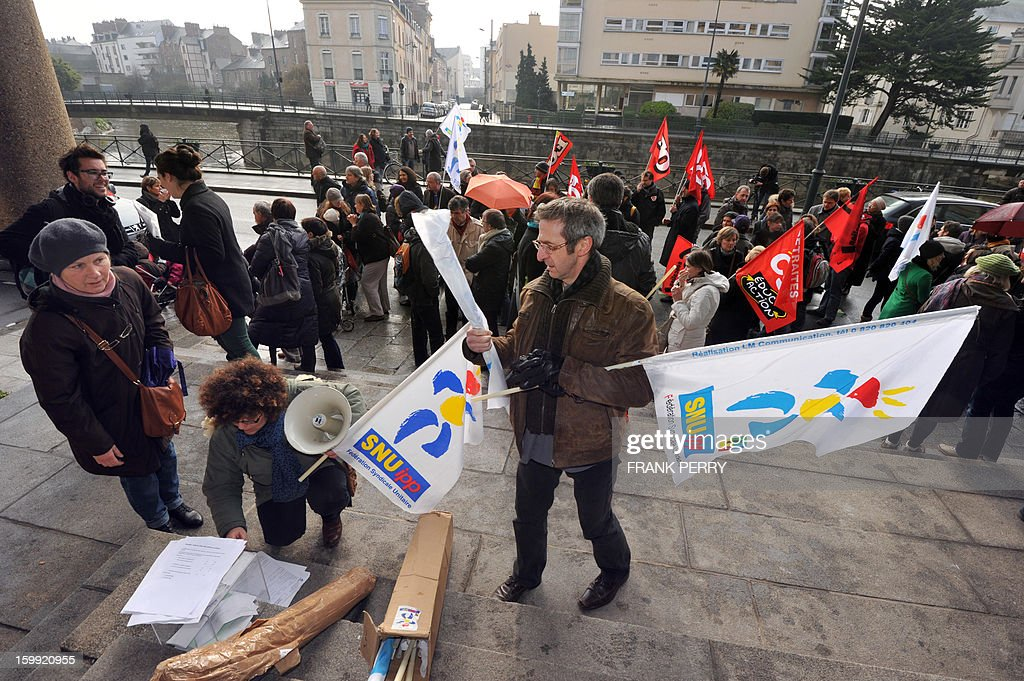 Activists hold union flags in front of the headquarters of the local office of the Education department, on January 23, 2013, in Rennes, as they take part in a nationwide strike and protest action against a proposed reform to increase the class time of primary school students. Around 80 people gathered in Rennes as several hundred other teachers gathered at protest rallies in various cities across the country.