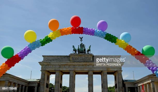 Activists hold up a balloon chain in rainbow colors as they demonstrate against homophobia and transphobia in front of the Brandenburg Gate on May 17...