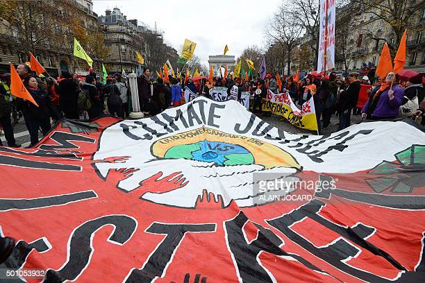 Activists hold up a giant banner reading 'Climate justice' by association 'ourpowercampaign' during a demonstration near the Arc de Triomphe at the...