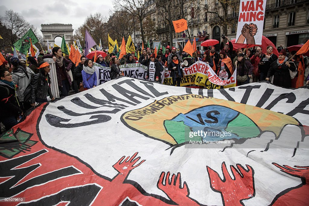 Activists hold up a giant banner reading 'Climate justice' by association 'our power campaign' during a demonstration near the Arc de Triomphe at the Avenue de la Grande Armee boulevard on December 12, 2015 in Paris, France. The final draft of a 195-nation landmark agreement on climate has been submitted at the United Nations conference on climate change COP21, aimed at limiting greenhouse gas emissions and keeping planetary warming below 2.0 degrees Celsius.