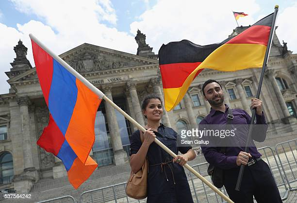 Activists hold up Armenian and German flags outside the Reichstag after parliamentarians at the Bundestag approved a resolution to recognize the 1915...