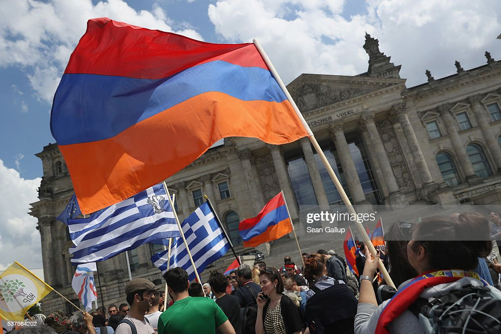 Activists hold up Armenian and Greek flags outside the Reichstag after parliamentarians at the Bundestag approved a resolution to recognize the 1915 Armenian genocide on June 2, 2016 in Berlin, Germany. The Bundestag approved a resolution recognizing the 1915-1916 deaths of hundreds of thousands of Armenians and other ethnic groups at the hands of Ottoman Turkish forces. The Turkish government has opposed any labeling of the deaths as genocide and the approval will likely irritate German-Turkish relations.