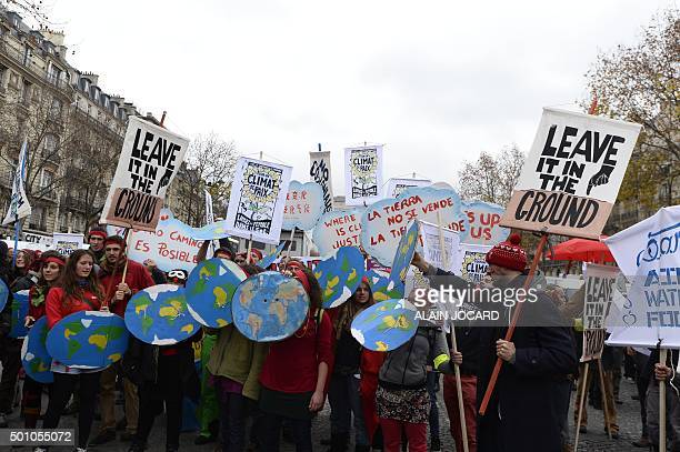 Activists hold up placards reading 'Leave it in the ground' during a demonstration at the Avenue de la Grande armee boulevard in Paris on December 12...