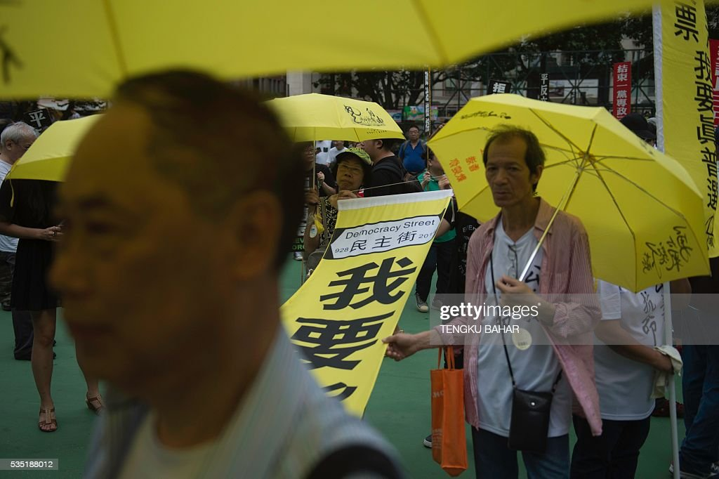 Activists hold yellow umbrellas - a symbol of Hong Kong's pro-democracy movement, and a banner ahead of the anniversary of the June 4, 1989 Tiananmen Square crackdown, in Hong Kong on May 29, 2016. People will gather in Hong Kong on June 4 for the annual remembrance ceremony to mark the 27th anniversary of the Tiananmen Square crackdown. / AFP / TENGKU