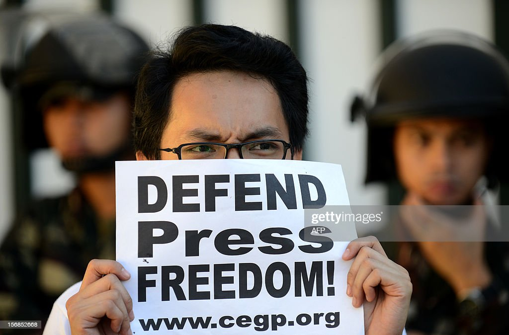 Activists holds a protest against impunity near the Department of National Defense building in Manila on November 23, 2012, during the third anniversary of the infamous November 23 massacre in Maguindanao province. Human Rights Watch on November 22 urged Aquino to do more to break up private armed groups, three years after 58 people were killed in the country's worst political massacre. AFP PHOTO/NOEL CELIS