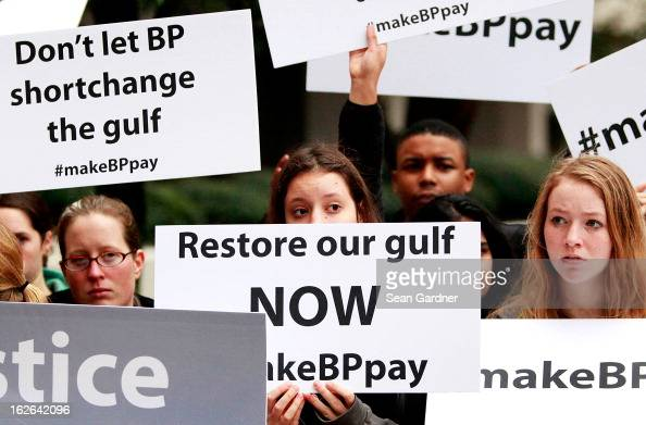 Activists holds signs during a protest in front of the Hale Boggs Federal Building on the first day of the trial over the Deep Water Horizon oil rig...