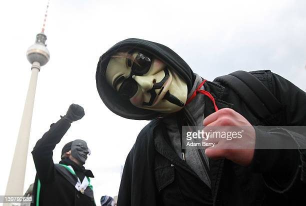 Activists in Guy Fawkes masks protest in front of the television tower during a demonstration against the AntiCounterfeiting Trade Agreement on...