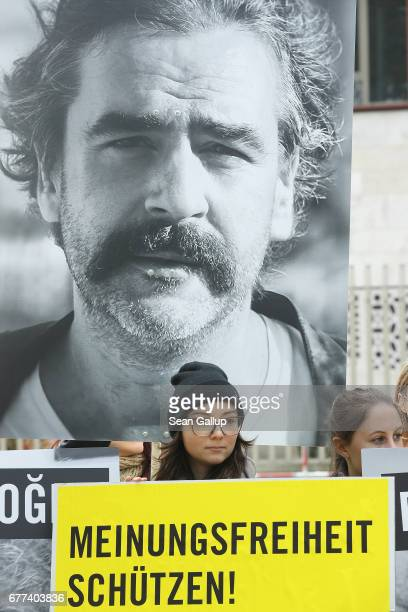 Activists including supporters of Reporters Without Borders and Amnesty International hold up the photos of journalists including TurkishGerman...