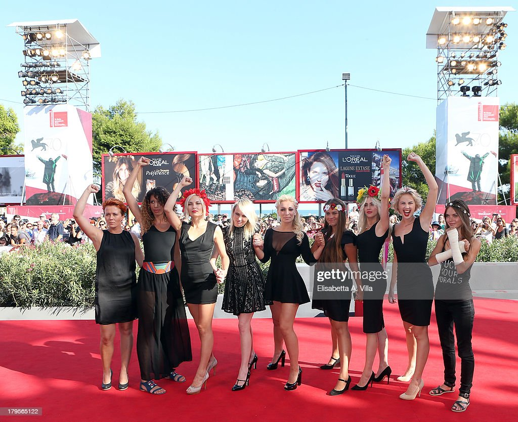 FEMEN activists Inna Shevchenko and Sasha Shevchenko pose with other members of the group on the red carpet before the 'Sacro GRA' Premiere during...